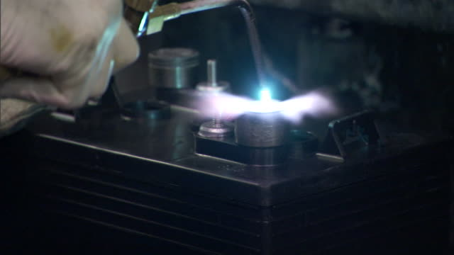 a production worker heats the posts on a wet-cell battery. - battery stock videos & royalty-free footage