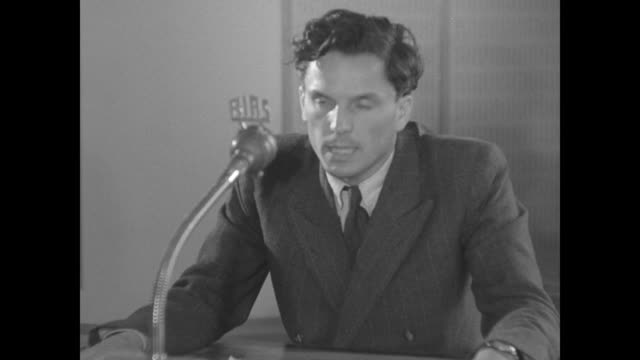 Production worker holds shot sign / Two shots of Rainer Hildebrandt as he sits at desk in front of microphone labeled RIAS and reads from notes...