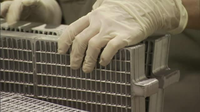vídeos de stock, filmes e b-roll de a production worker sorts lead plates in a battery factory. - operário de linha de produção