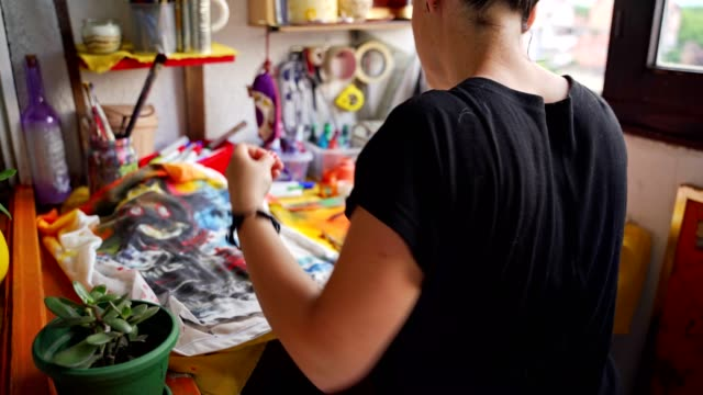 productive female artist working in her messy workshop - maglietta video stock e b–roll
