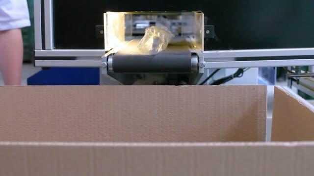 生産の終わりに箱に入る産業コンベヤーベルトのシリーズ生産のプロダクトは行く準備ができている - 梱包機点の映像素材/bロール