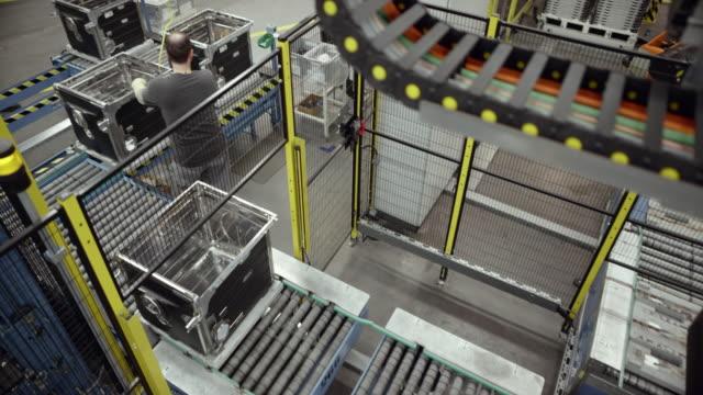 vidéos et rushes de cs produits circulant sur le tapis roulant à un poste de travail où les employés de sexe masculin serrer les vis sur les produits - slovénie