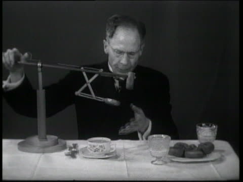 b/w 1937 prof. i.m. demonstrating his invention for dunking doughnuts without dripping / newsreel - erfindung stock-videos und b-roll-filmmaterial
