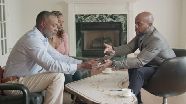 professional advisor meets with couple in the home - financial advisor stock videos & royalty-free footage