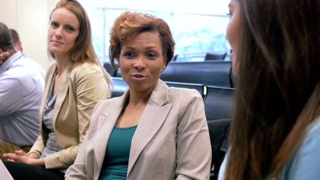 Professional African American businesswoman talking to colleague during seminar