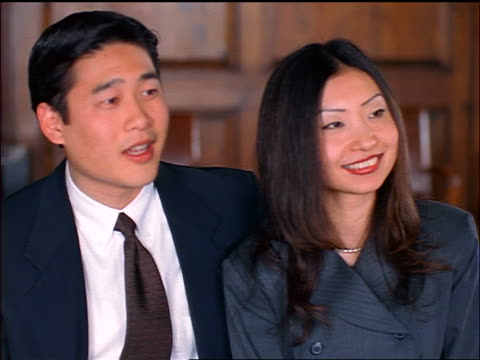 stockvideo's en b-roll-footage met professional asian couple smiling, talking + nodding to someone offscreen in office - compleet pak