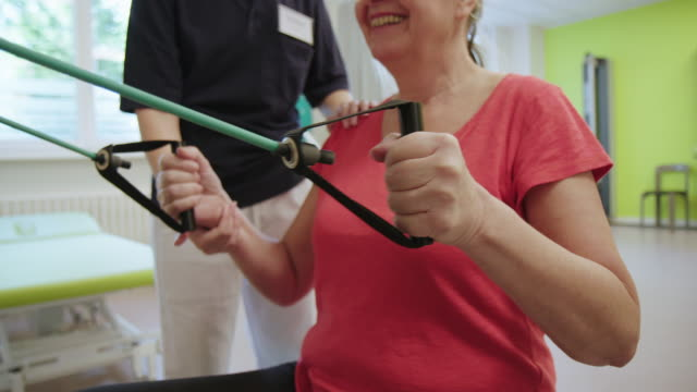 Professional assisting woman with resistance band