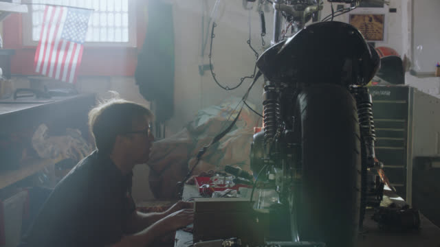 Professional auto mechanic inspects motorcycle on work table in repair shop.