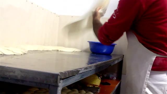 Professional baker throwing in the air and rolling Burek (Börek) dough