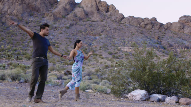 Professional ballroom dancers perform elegant choreographed routine in barren desert setting.