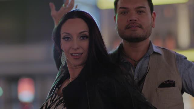 vídeos de stock e filmes b-roll de slo mo. professional ballroom dancers twirl and strike dramatic pose for camera on las vegas strip at night. - grupo multiétnico