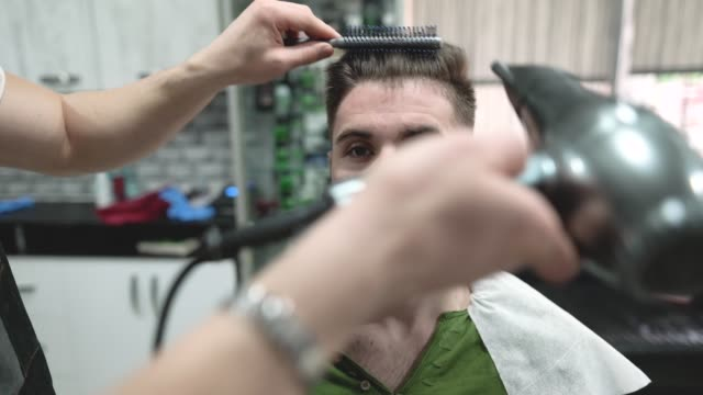 professional barber blow drying client's hair - blow drying hair stock videos and b-roll footage