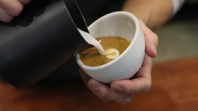 stockvideo's en b-roll-footage met professionele barista gieten gestoomde melk in witte koffiekopje maken prachtige latte art rosetta patroon. - foam hand