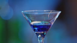 Professional barman decorates a blue cocktail with ice  . Bartender prepares cocktails on defocused background and pours and serves a cocktail . Barman preparing colorful cocktail . Slow Motion .