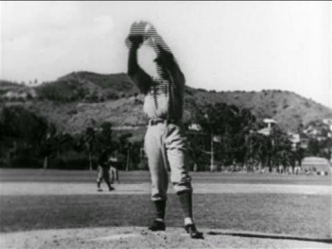 vídeos y material grabado en eventos de stock de b/w 1938 professional baseball player pitching ball in practice game / chicago cubs / california - uniforme de béisbol