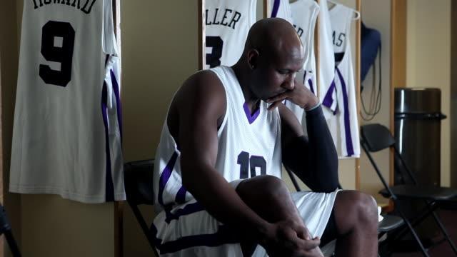 vídeos de stock, filmes e b-roll de cu pan professional basketball player in locker room mentally preparing for game / washington, usa - com as mãos na cabeça