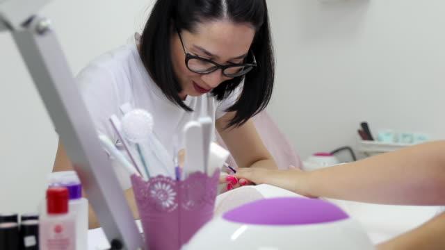 vidéos et rushes de ongles professionnels de peinture d'esthéticienne de peinture au salon de manucure - se faire dorloter