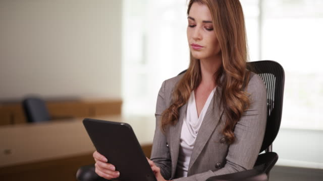 Professional Businesswoman in her 20s using tablet while sitting on her chair