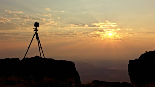 Professional camera silhouette on cliff running timelapse at sunrise