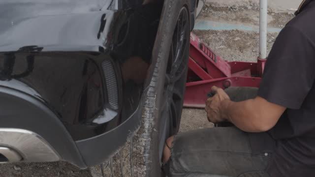 stockvideo's en b-roll-footage met professionele auto mechanicus veranderende wiel in auto repair shop. in een garage - piercen