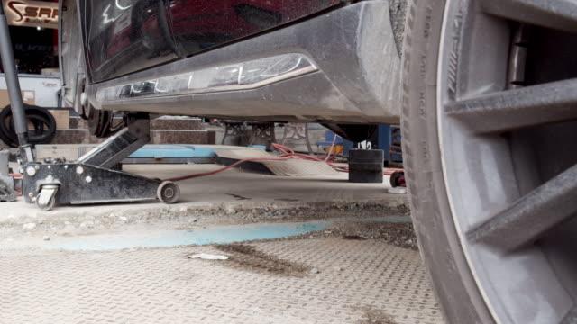 stockvideo's en b-roll-footage met professionele auto mechanicus tilde een zwarte auto voor het repareren van een wiel - piercen