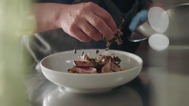 vídeos y material grabado en eventos de stock de professional chef adds microgreens to seared tuna steak while plating - acero inoxidable