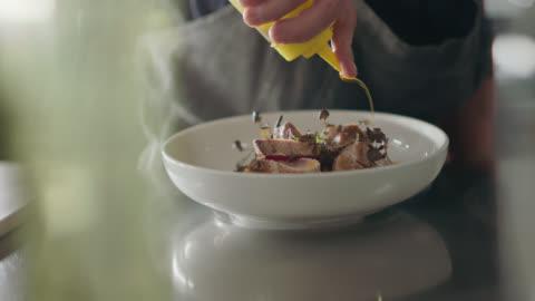 slo mo. professional chef adds oil to seared tuna steak while plating - stål bildbanksvideor och videomaterial från bakom kulisserna