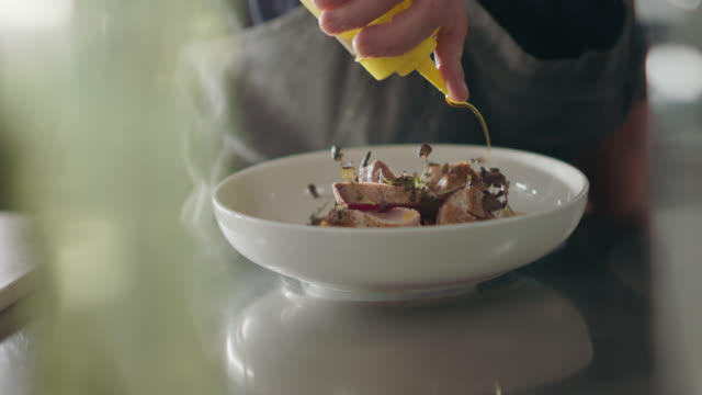 stockvideo's en b-roll-footage met slo mo. professional chef adds oil to seared tuna steak while plating - staal