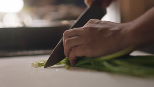 slo mo. professional chef chops scallions on a cutting board - küchenmesser stock-videos und b-roll-filmmaterial