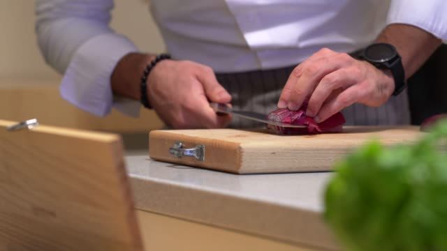 professional chef cooking in domestic kitchen: cutting tropea red onion - red onion stock videos & royalty-free footage