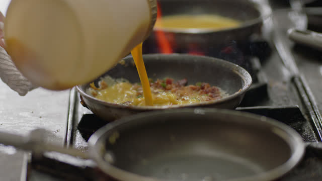 slo mo. professional chef cooks scrambled eggs with bacon in a pan over a flaming stove in a commercial kitchen at a diner. - switch stock videos & royalty-free footage