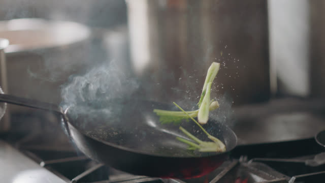 slo mo. professional chef flips fennel and salt in a frying pan - sprinkling stock videos & royalty-free footage