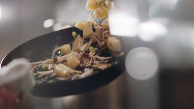 vídeos de stock, filmes e b-roll de slo mo. professional chef flips mushrooms and vegetables in a frying pan - preparando comida