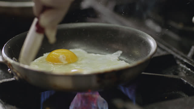 vídeos de stock, filmes e b-roll de professional chef fries an egg in a pan over a flaming stove top in a commercial kitchen of a diner. - gema de ovo