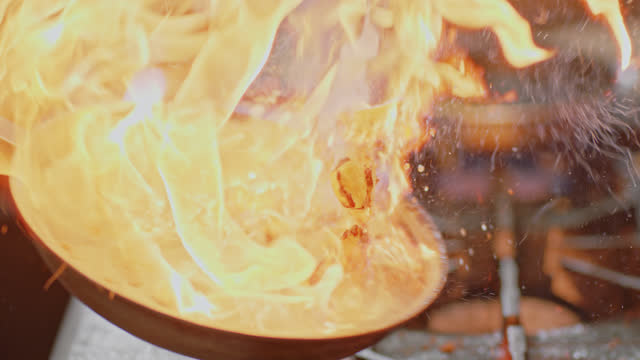 slo mo. professional chef fries bananas in a pan over a flaming stove in a commercial kitchen at a diner. - garkochen stock-videos und b-roll-filmmaterial