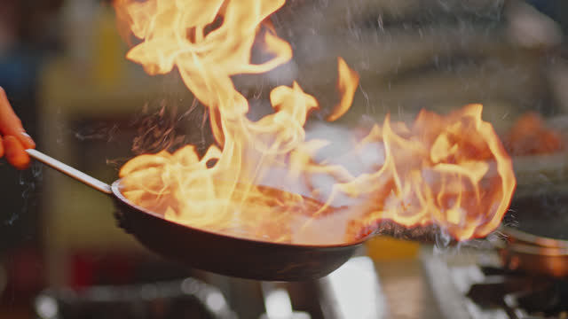 slo mo. professional chef fries bananas in a pan over a flaming stove in a commercial kitchen at a diner. - preparing food stock videos & royalty-free footage