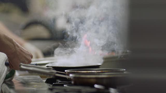 vídeos y material grabado en eventos de stock de slo mo. professional chef lifts lid off pan and cooks eggs over a flaming stove top in a commercial kitchen of a diner. - utensilio para cocinar