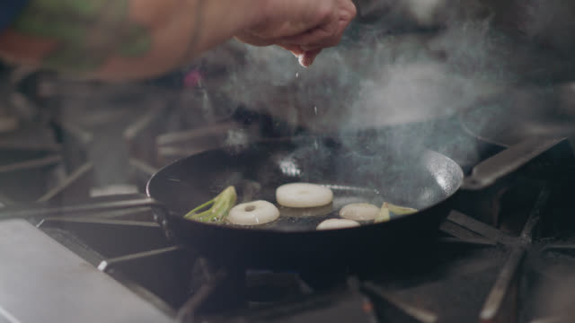 slo mo. professional chef moves fennel and onions around in a frying pan - steam stock videos & royalty-free footage