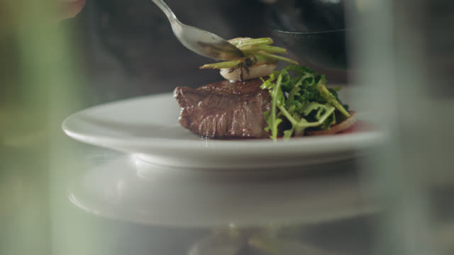 slo mo. professional chef plates steak from cast iron pan and adds garnish on top - steak stock videos & royalty-free footage