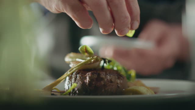 stockvideo's en b-roll-footage met slo mo. professional chef plates steak from cast iron pan and adds microgreens to the plate - kok