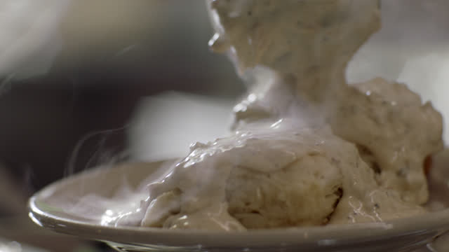slo mo. cu. a professional chef scoops steaming hot sausage gravy onto two biscuits at an authentic diner - biscuit stock videos & royalty-free footage