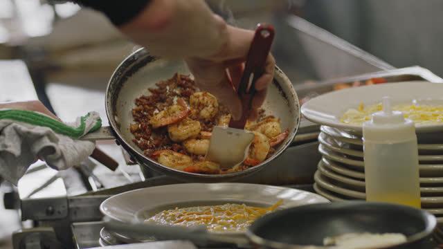 vídeos de stock e filmes b-roll de cu. professional chef scrapes shrimp and crispy bacon pieces onto a plate of cheese grits in a commercial kitchen - camarão
