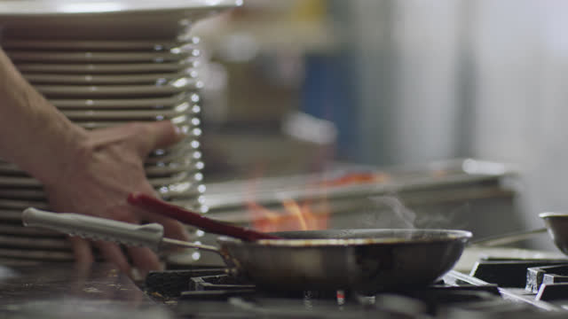 slo mo. professional chef sets down a stack of plates next to a pan over a flaming stove top in a commercial kitchen of a diner. - stack of plates stock videos & royalty-free footage