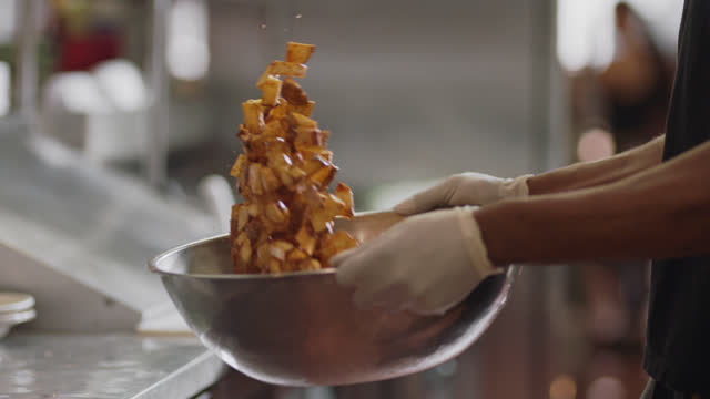 slo mo. professional chef shakes and flips fried potatoes in a large metal bowl in the commercial kitchen of a diner. - glove video stock e b–roll
