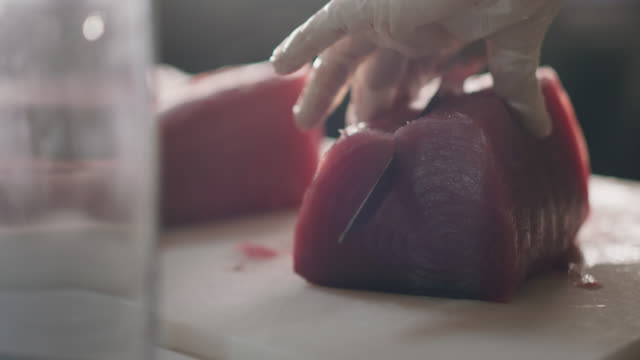 vídeos de stock e filmes b-roll de professional chef slices a piece of raw tuna in half - marisco