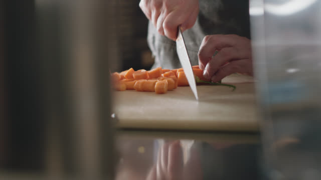 professional chef slices raw carrots with a large kitchen knife - chopped stock videos & royalty-free footage