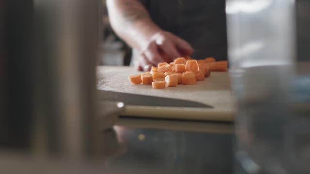 professional chef slides freshly chopped carrot slices into a metal bowl - carota video stock e b–roll