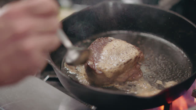 slo mo. professional chef spoons melted butter onto steak in a cast iron pan - heat temperature stock videos & royalty-free footage