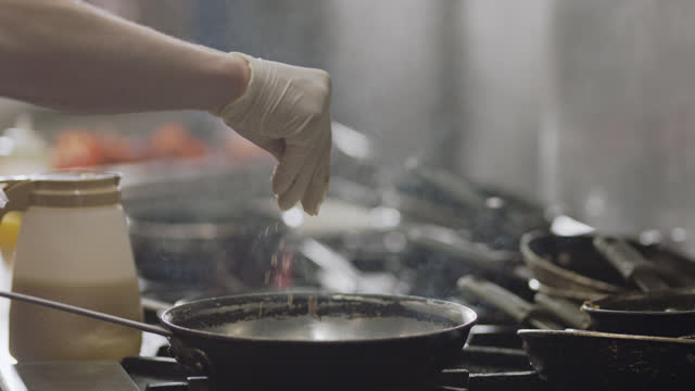 slo mo. professional chef sprinkles brown sugar in a pan over a flaming stove top in a commercial kitchen of a diner. - cibi surgelati video stock e b–roll