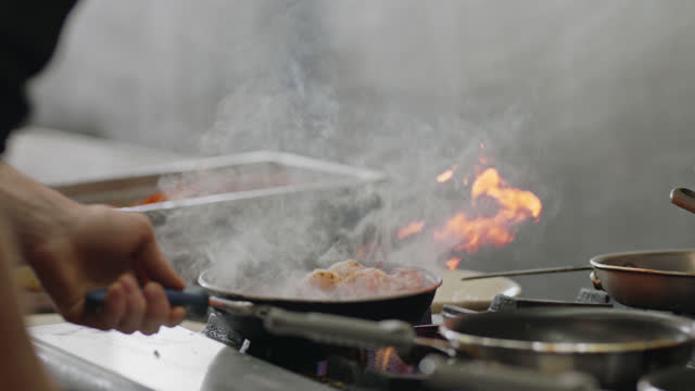 slo mo. professional chef sprinkles crispy bacon into a pan of shrimp cooking over a flaming stove in a commercial kitchen - bacon stock videos & royalty-free footage